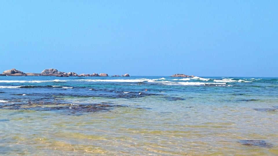 See the waves breaking on the outer reef and black structure of the inner Hikkaduwa Coral Reef.