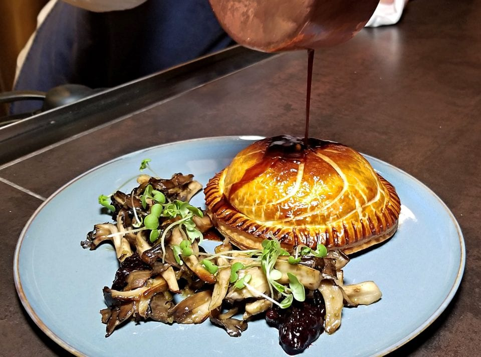 Venison-Pie-w-Pan-seared-mushrooms-w-red-win-jus-being-poured-on at Chez Muffy
