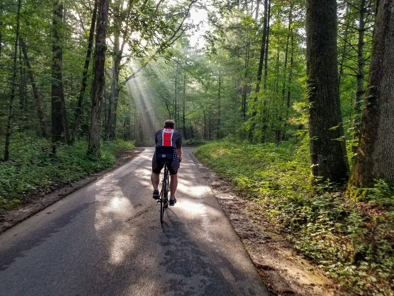 Biking Cades Cove with streaks of sunlight bursting through the trees