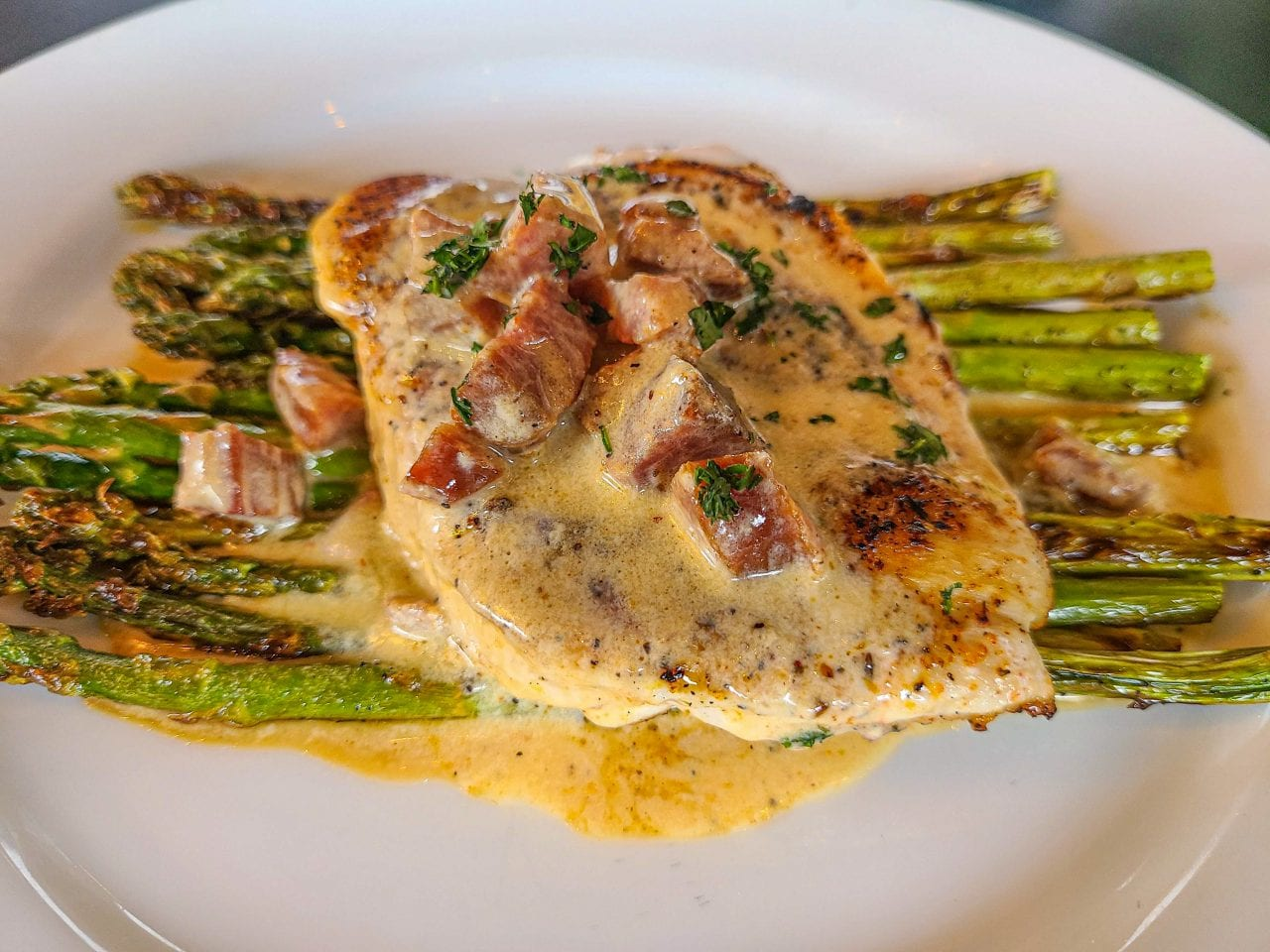 Patio 44 blackened chicken in a Cajun cream sauce over grilled asparagus