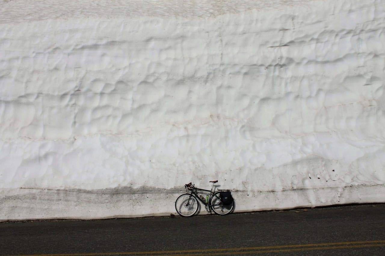 Bike against snowbank Glacier National Park photo via Brian Schott